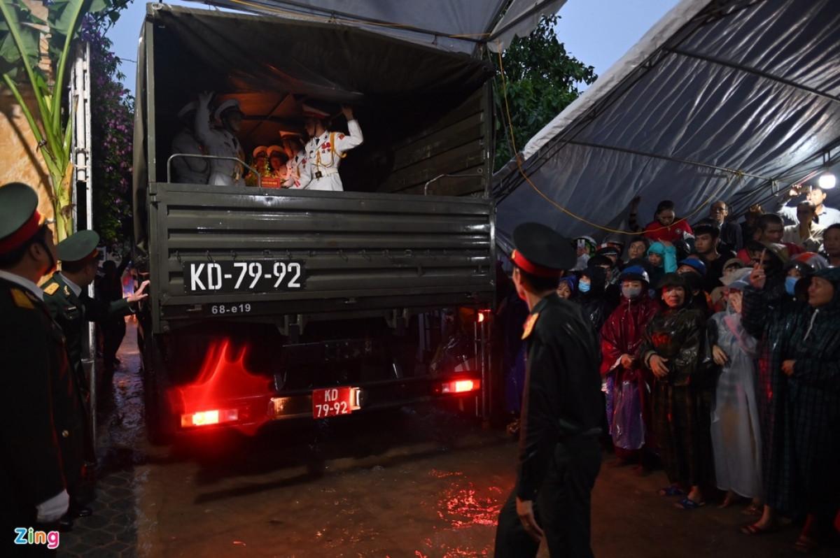 Linh cữu thiếu tướng được đoàn tiêu binh cùng bộ đội đưa vào nhà trong khi trời mưa lớn.