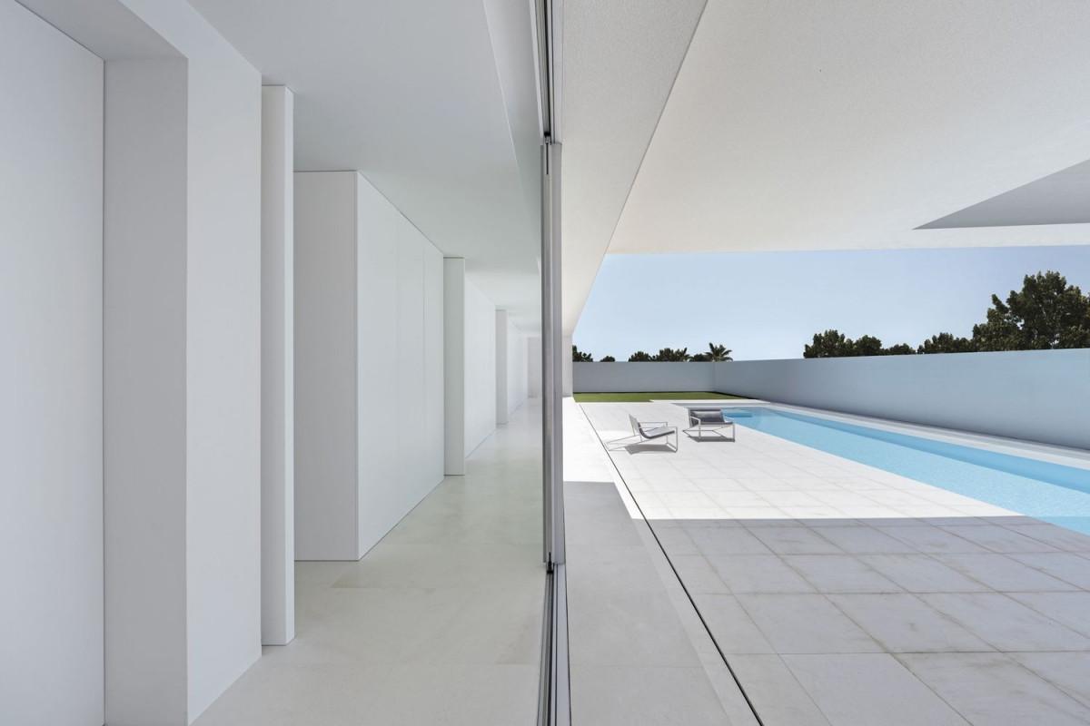 Khối kiến trúc phía dưới nhìn ra hồ bơi có 4 phòng ngủ, được kết nối bởi một hành lang chạy dài. Vách kính lớn bên ngoài hành lang cho phép mở rộng tầm nhìn tối đa. Tường, trần, sàn đều sử dụng màu trắng.