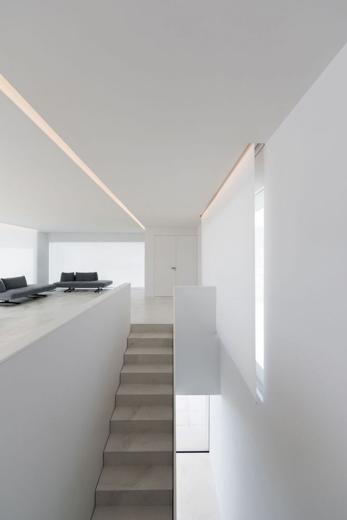 Tầng 2 là không gian phòng khách liên thông với phòng bếp – ăn. Bộ sofa màu đen như một điểm nhấn trên nền trắng.