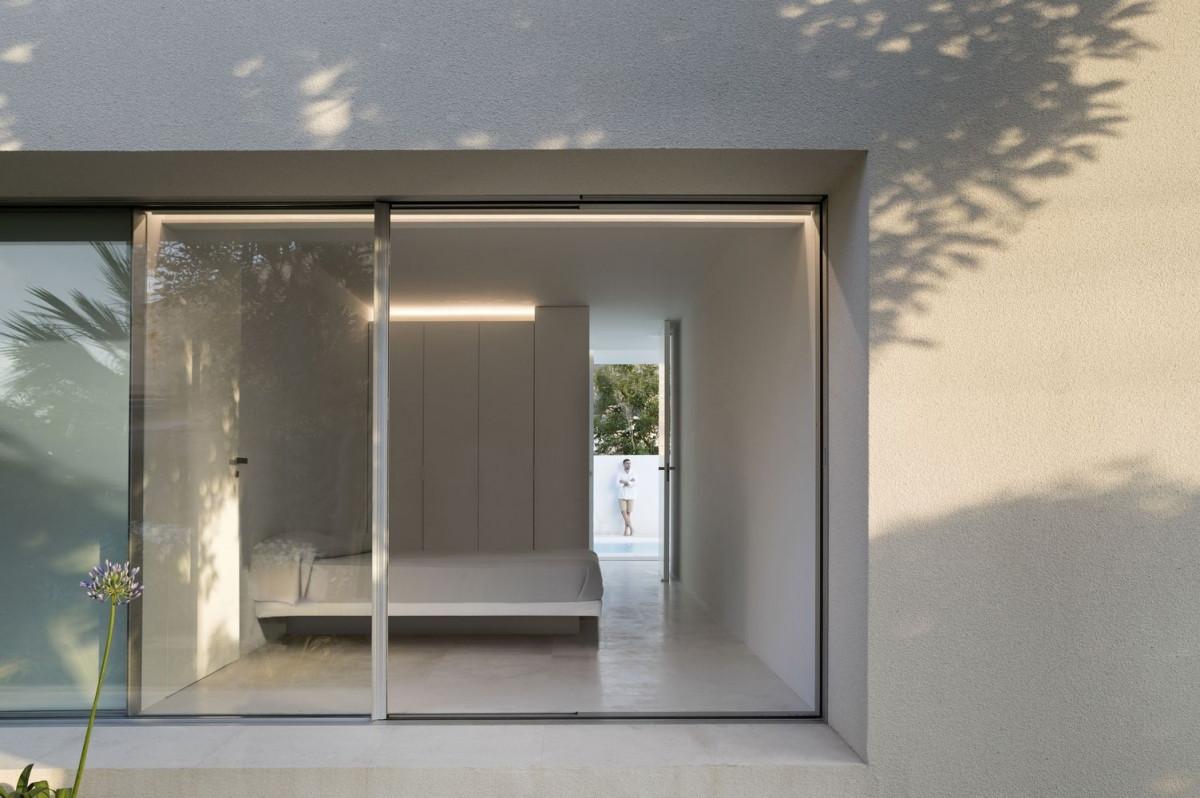Các phòng ngủ có vách kính lớn mở ra vườn sau nhà. Nội thất cũng cùng phong cách tối giản với màu chủ đạo là màu trắng.