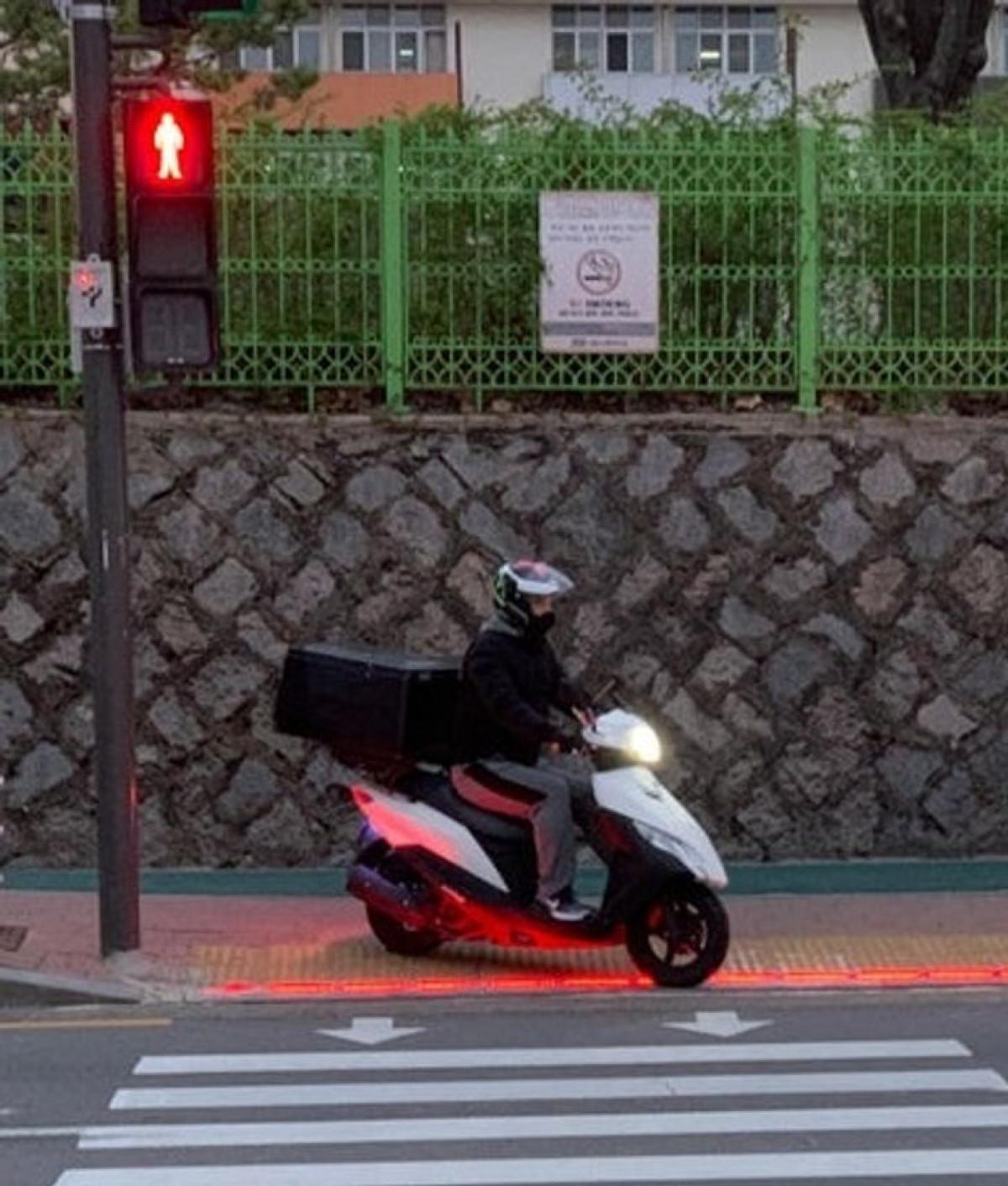 Trong một thế giới mà chúng ta dành ngày càng nhiều thời gian vào màn hình điện thoại, các nhà quản lý đô thị tại Hàn Quốc đã nghĩ ra một sáng kiến giúp các cư dân của thế giới hiện đại không bị lỡ đèn tín hiệu giao thông trong khi đang sử dụng thiết bị di động. Theo đó, các cột đèn giao thông có thêm bóng đèn ở thấp gần mặt đường để khi người tham gia giao thông cúi mặt vào màn hình thiết bị di động, họ có thể dễ dàng nhận biết được khi nào đèn tín hiệu chuyển từ đỏ sang xanh để khởi hành.